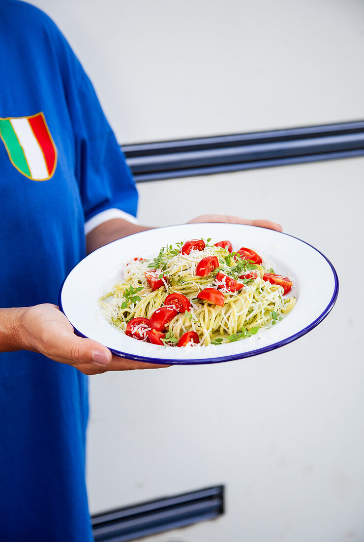 A woman serving a plate of spaghetti with pesto and cherry tomatoes