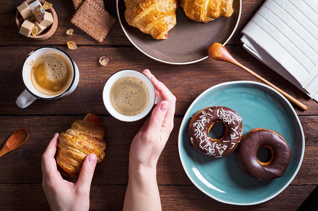 Hand hält Kaffeebecher, Croissant und Donuts