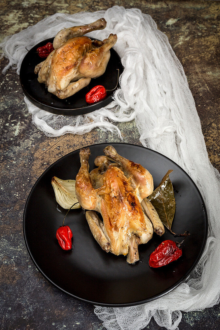 Roast chicken with onions, garlic, peppers and aromatic herbs