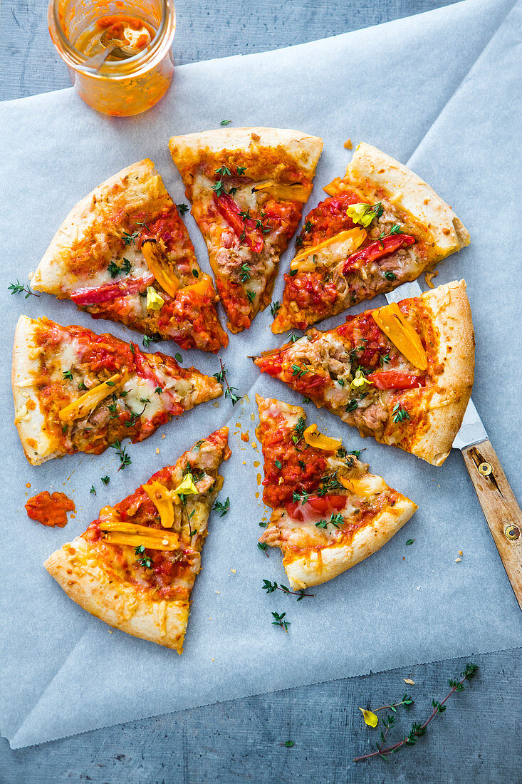 A pizza with tuna, ajvar, peppers, tomatoes, thyme and alpine cheese
