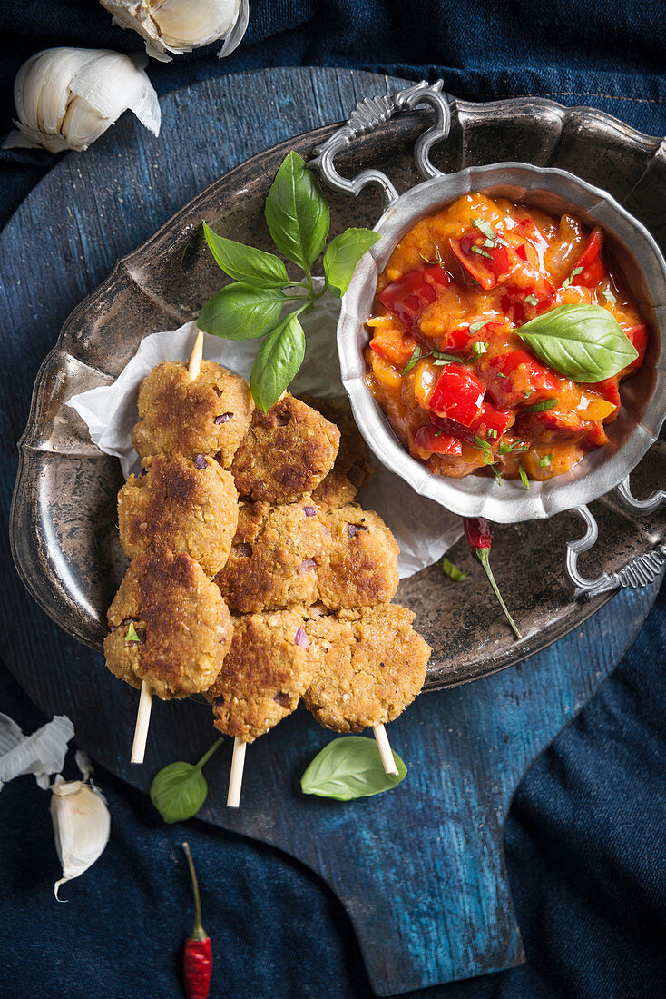 Chickpea fritters on sticks with a fiery pepper and tomato salsa, vegan