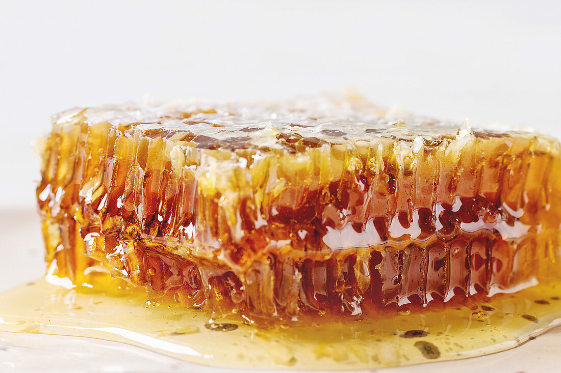 Organic honey in honeycombs on white marble background