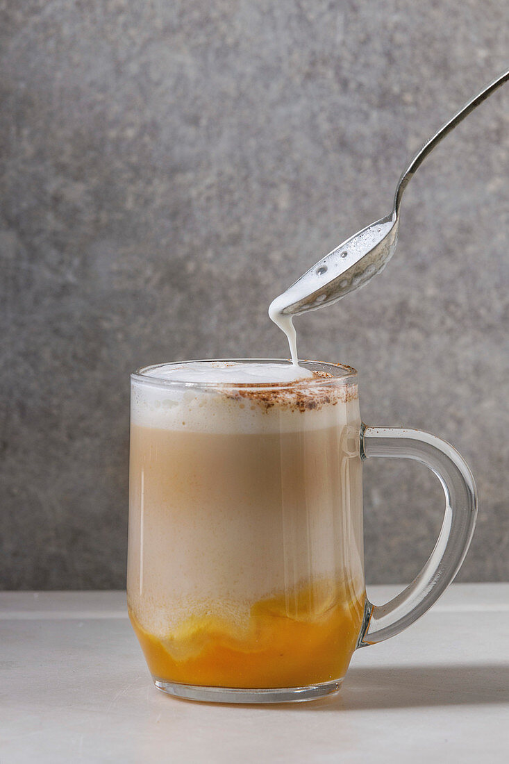 Glass of pumpkin layered spice latte with pumpkin puree, milk foam flowing from spoon and cinnamon