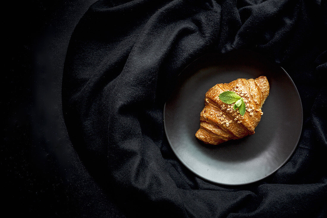 Gebackenes Croissant auf schwarzem Teller