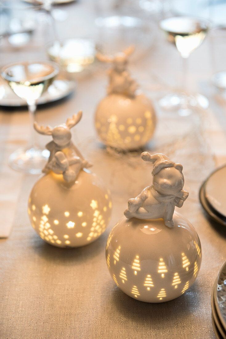 Illuminated porcelain spheres topped by whimsical animal figurines with a festive theme