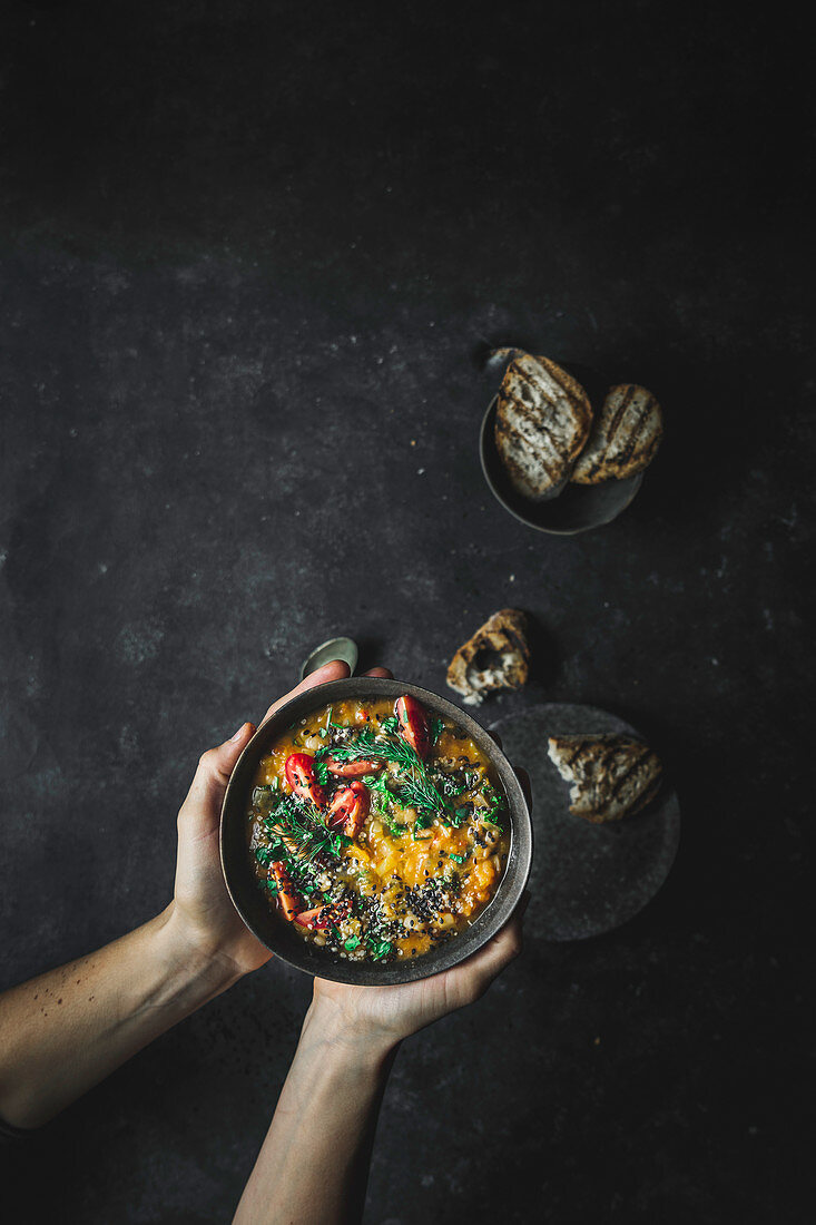 Colourful vegetable and white bean soup on dark background