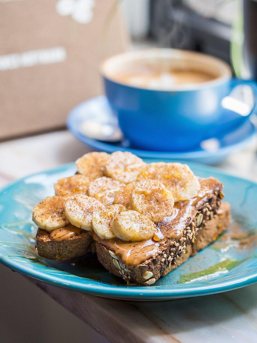 Whole grain sourdough toast wih organic almond butter, banana, honey and cinnamon