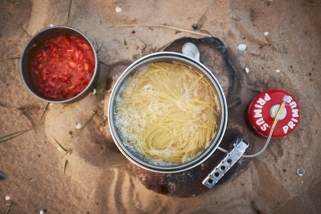 Noodles being cooked on a gas burner