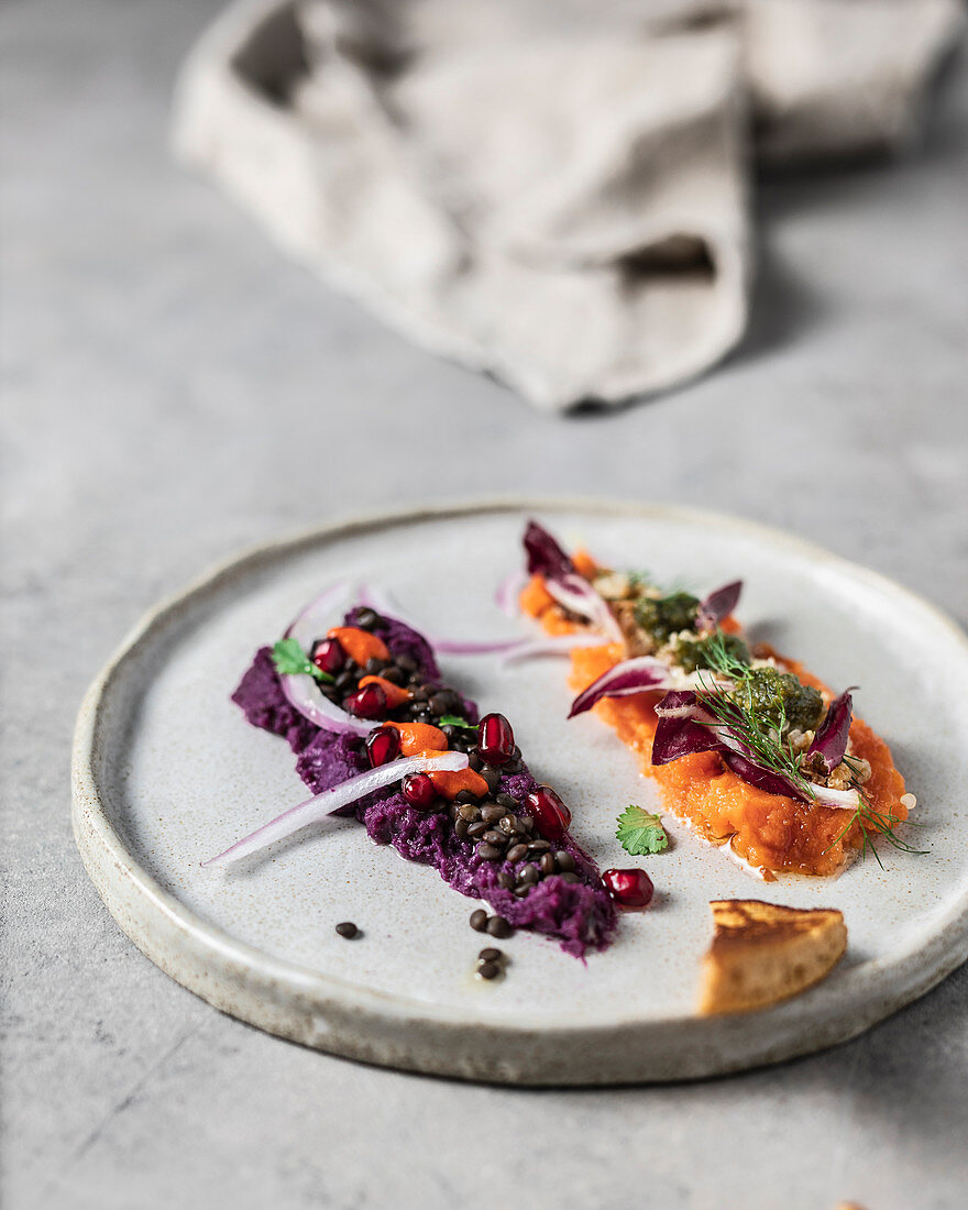 Orange and purple mashed sweet potato artfully topped with healthy stuff