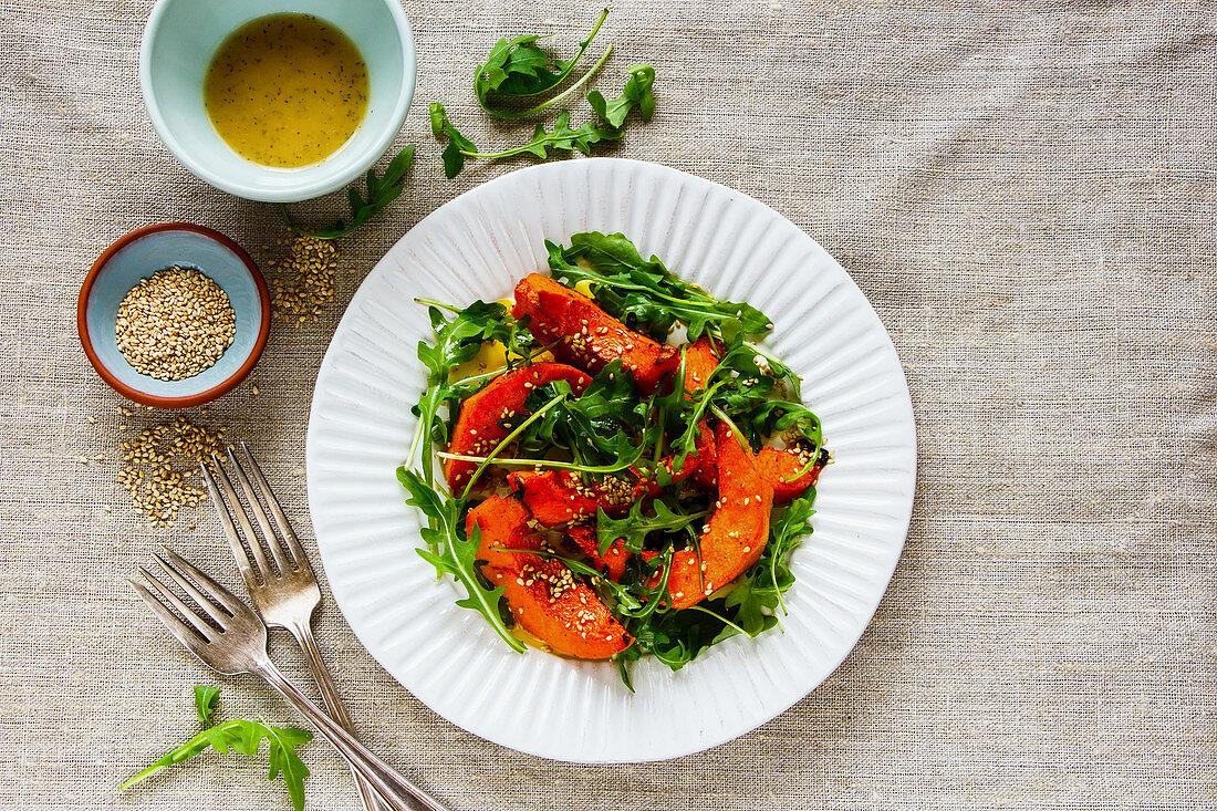 Sesame seed pumpkin with arugula salad