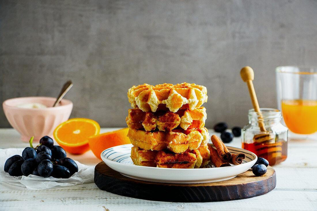 Delicious breakfast with warm cinnamon waffles, fresh fruit and orange juice