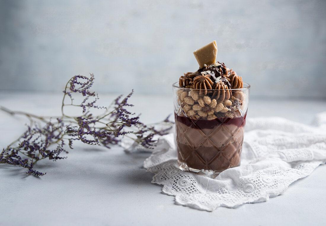 A vegan dessert made from chocolate pudding, chocolate quark, raspberry jam, popped oats, chocolate butter cream and chocolate