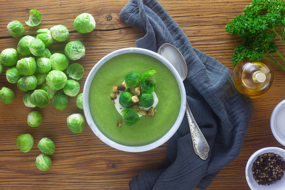 Cream of Brussels sprout soup with ingredients on a wooden surface