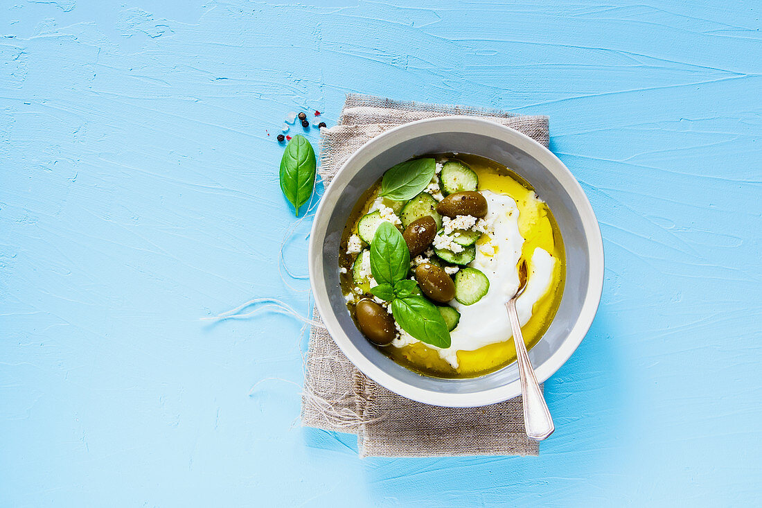 Healthy yogurt, olives, feta cheese, cucumber, olive oil and basil