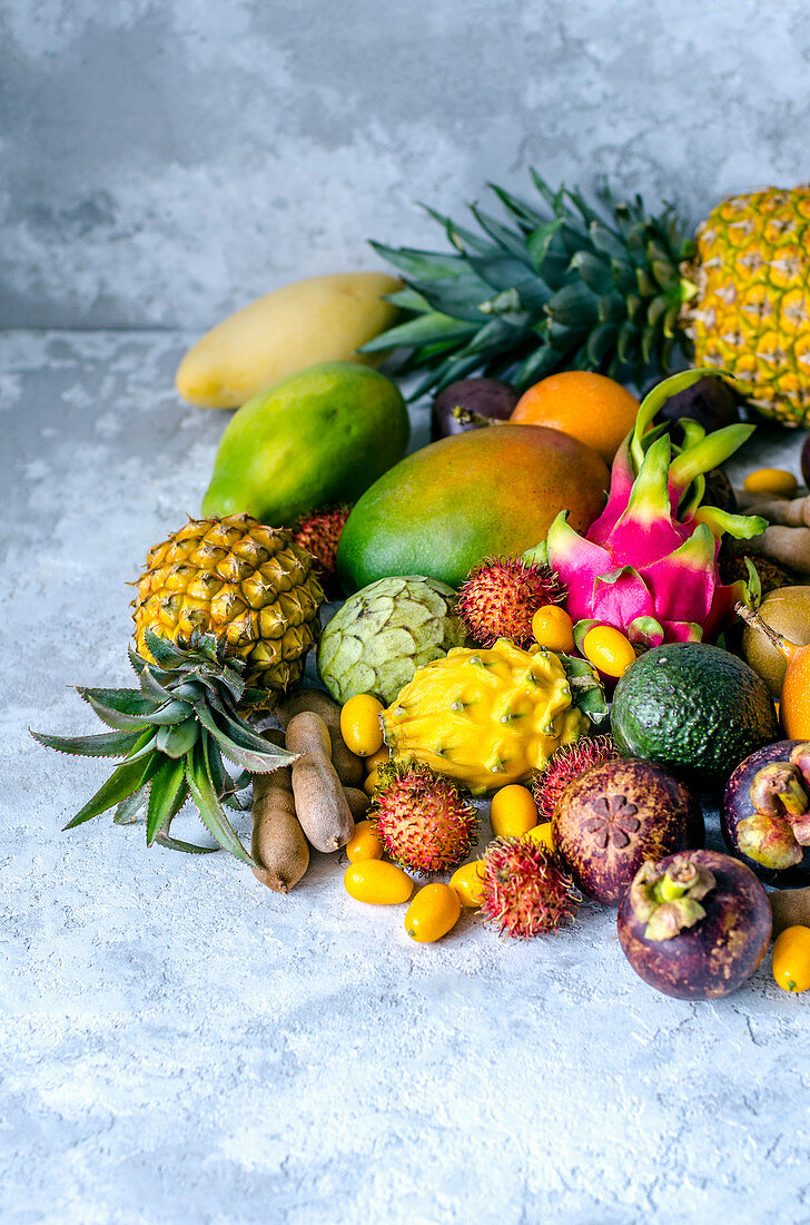 A large pile of assorted fresh and tasty tropical fruits on a gray background