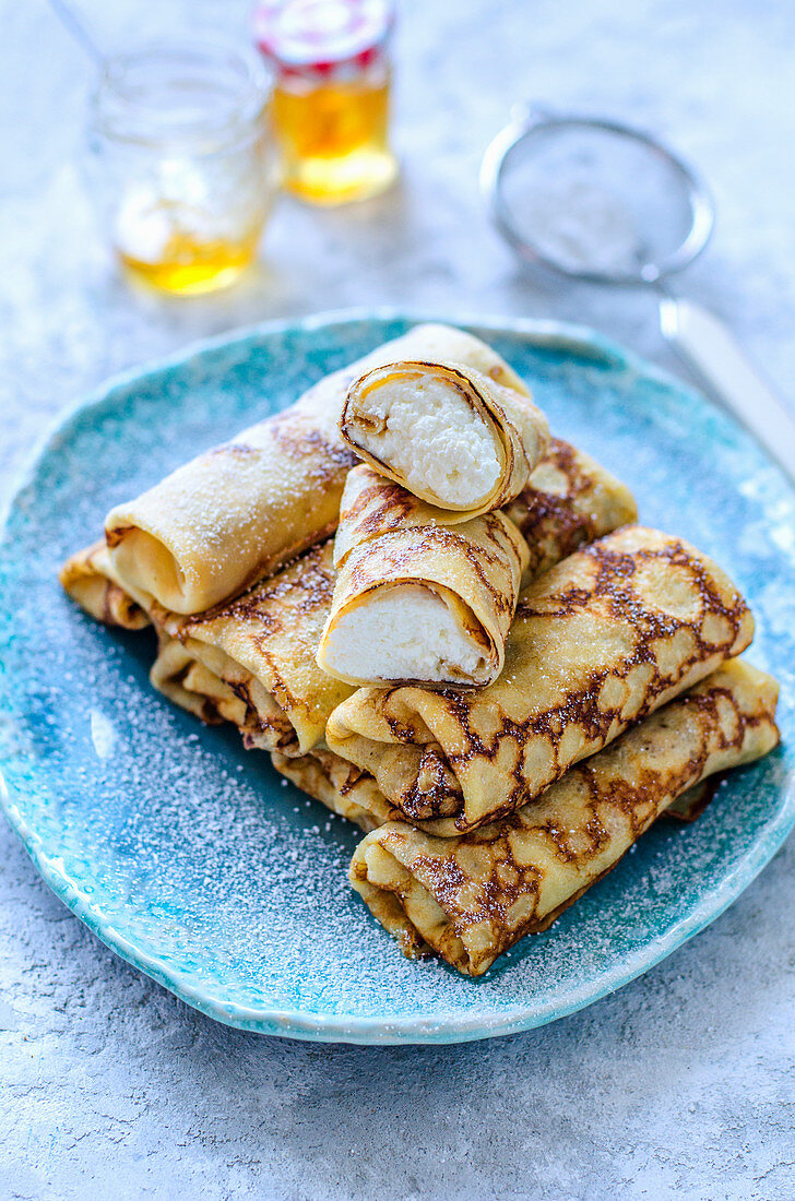 Thin pancakes stuffed with cottage cheese a jar of honey on blue plate