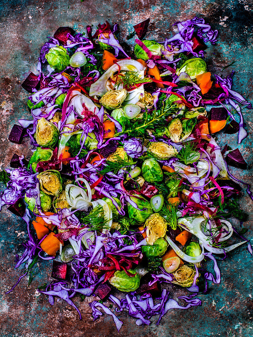 Abstract color composition of different sliced vegetables on a colored surface