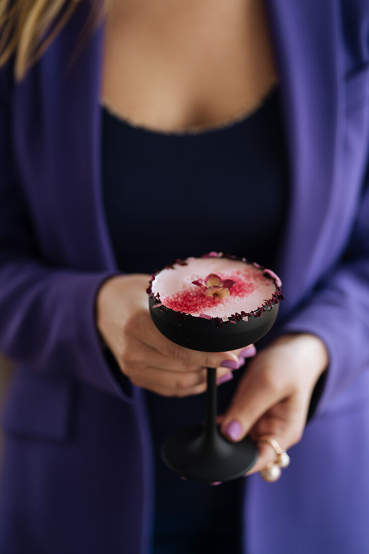 A raspberry cocktail with a rosebud rim