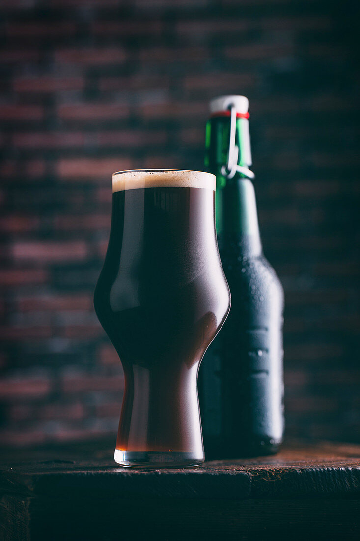 A glass of dark beer with a closed bottle of beer in the background