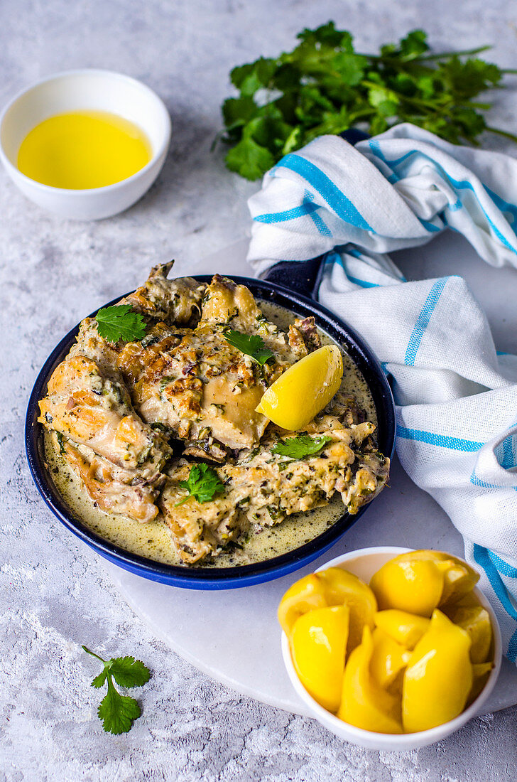 Chicken in a garlic-cream sauce in a ceramic pan and pickled lemons (One pot dish)