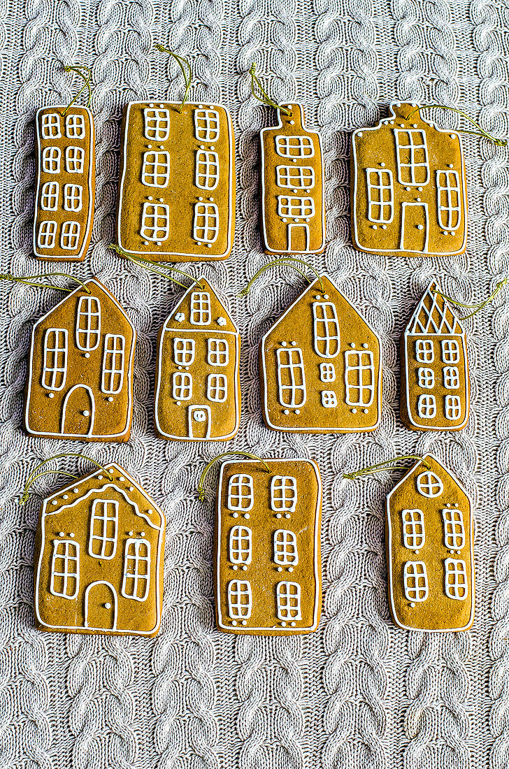Gingerbread houses with golden ropes to decorate the Christmas tree on a knitted surface