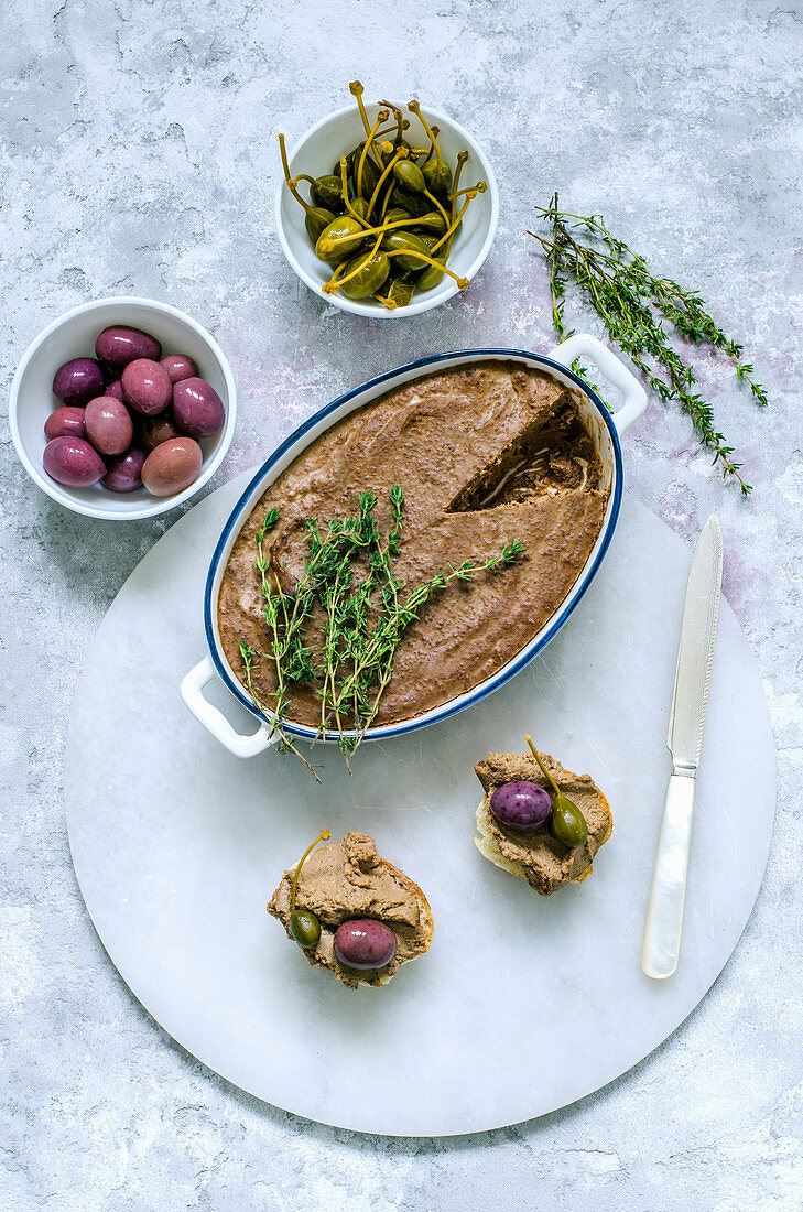Liver pate in ceramic form, decorated with fresh thyme and two baguette sandwiches with pate, capers, olives on a marble stand