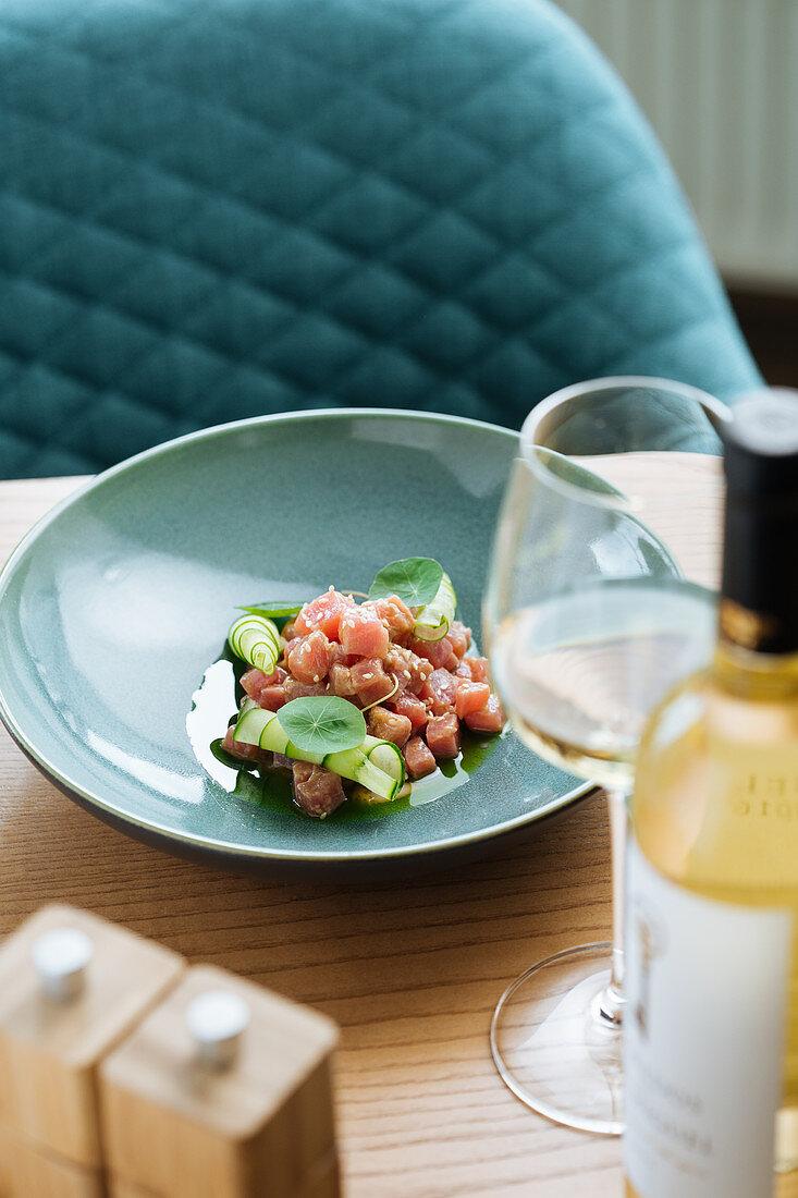 Fischtatar serviert mit Weißwein auf Restauranttisch