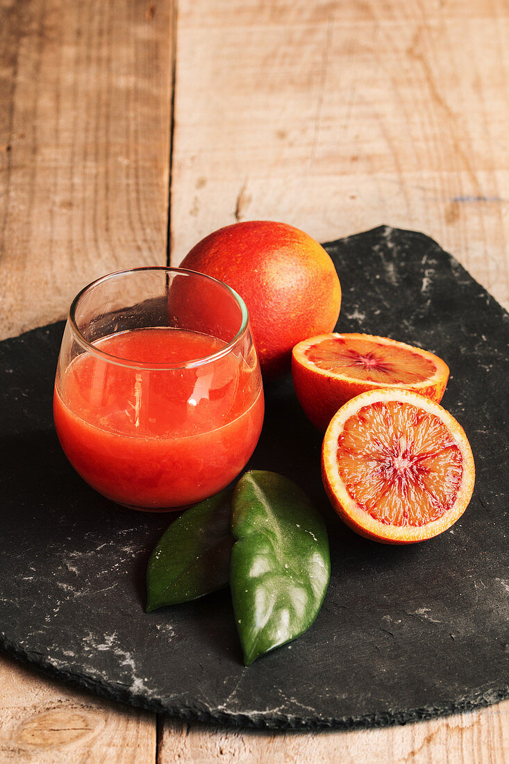 Blood orange juice in a glass with blood oranges