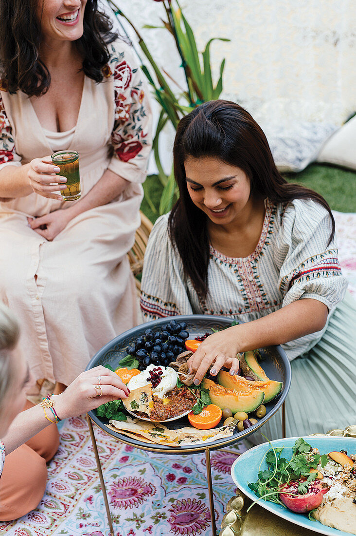Girlfriends celebrating outdoors with Moroccan dishes