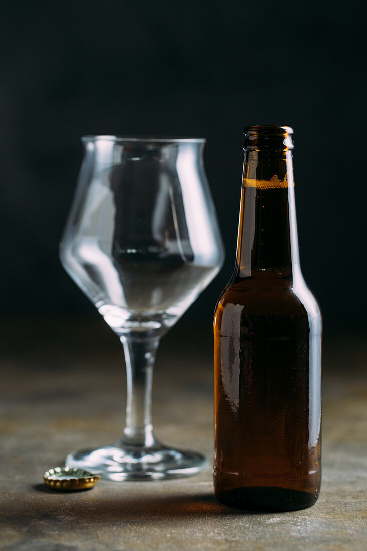 A bottle of beer with an empty beer glass and a bottle cap