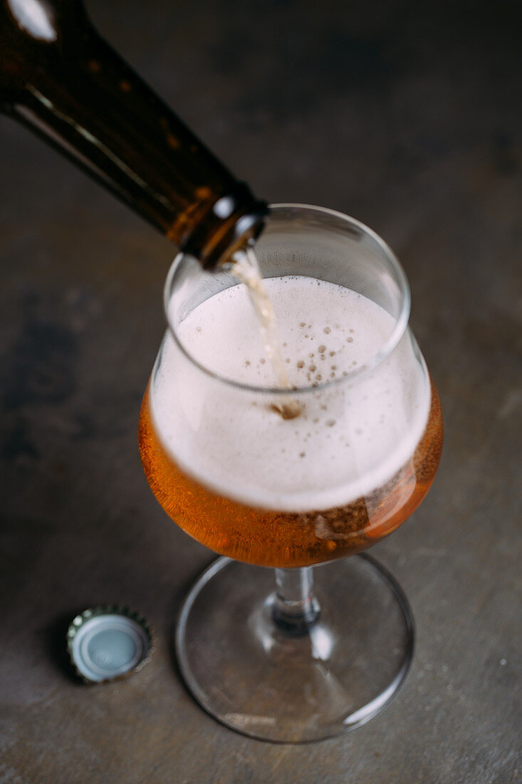 Beer being poured from a bottle into a beer glass