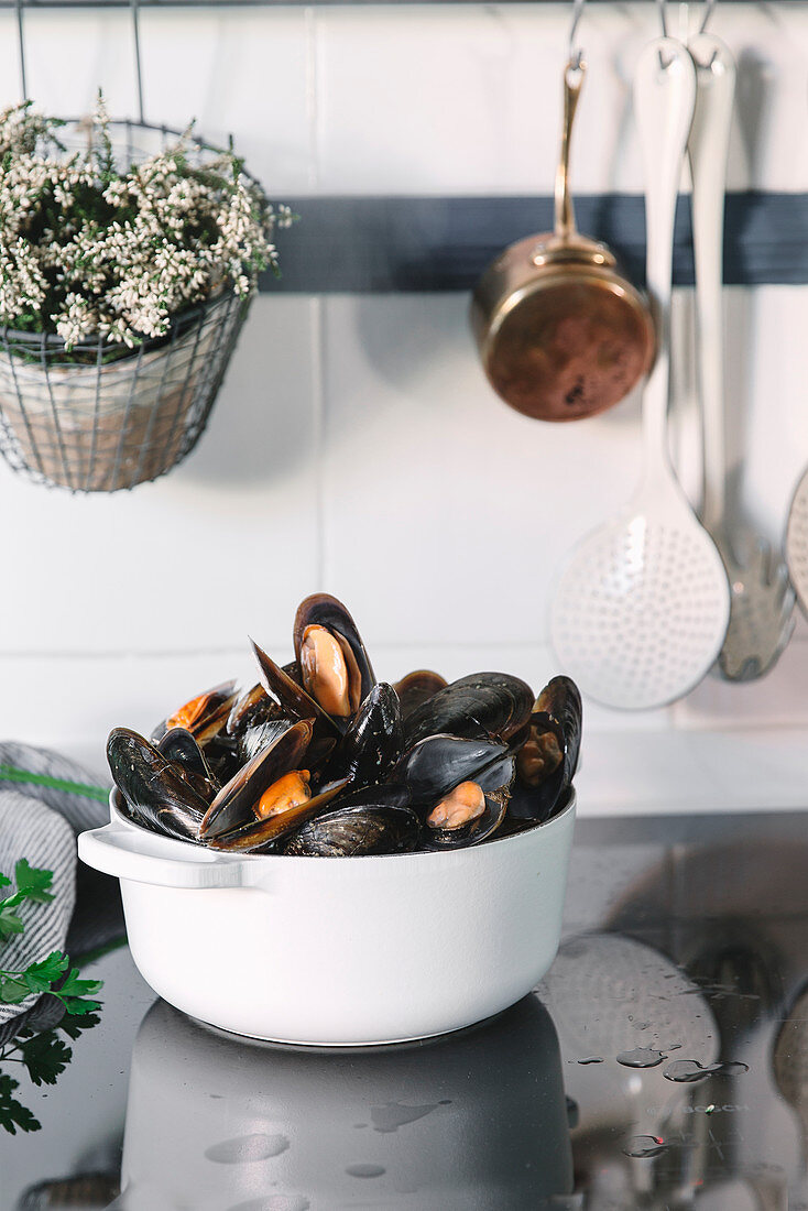 A bowl of mussels on a kitchen work surface