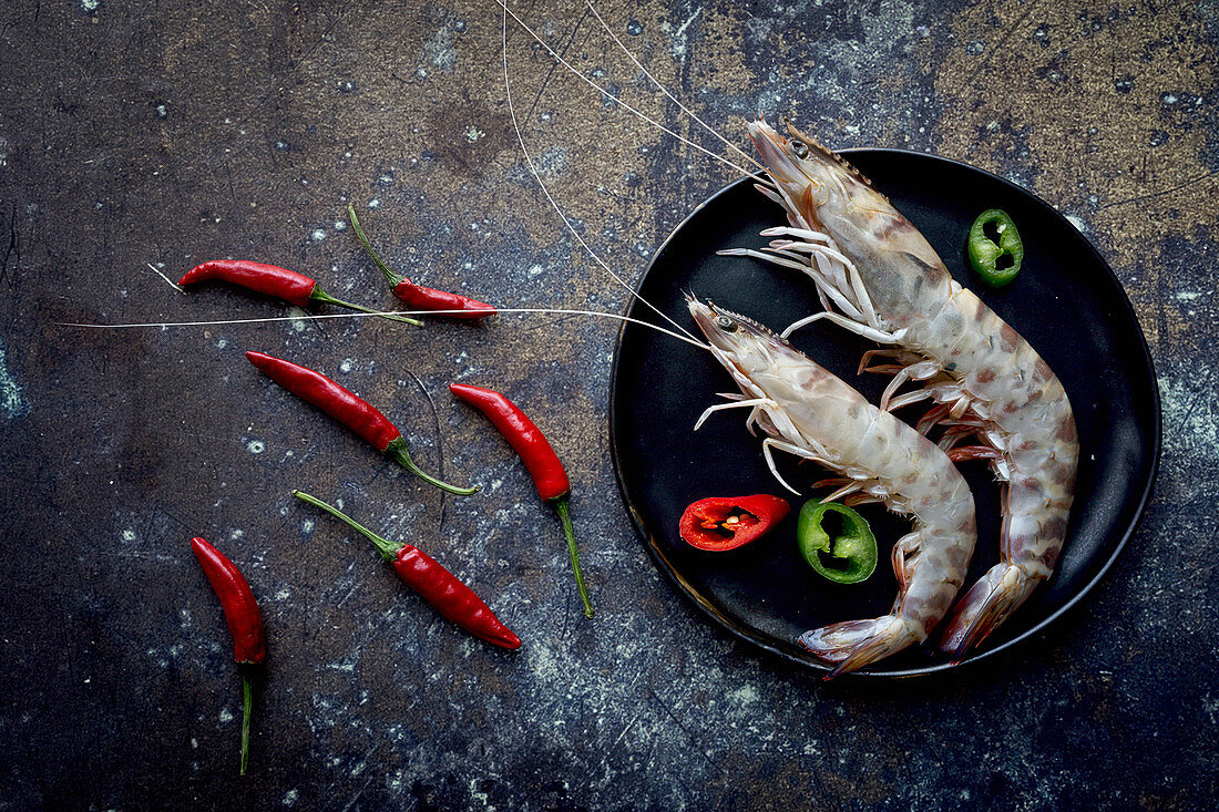 Small hot peppers lying near plate with delectable boiled shrimps on dark tabletop