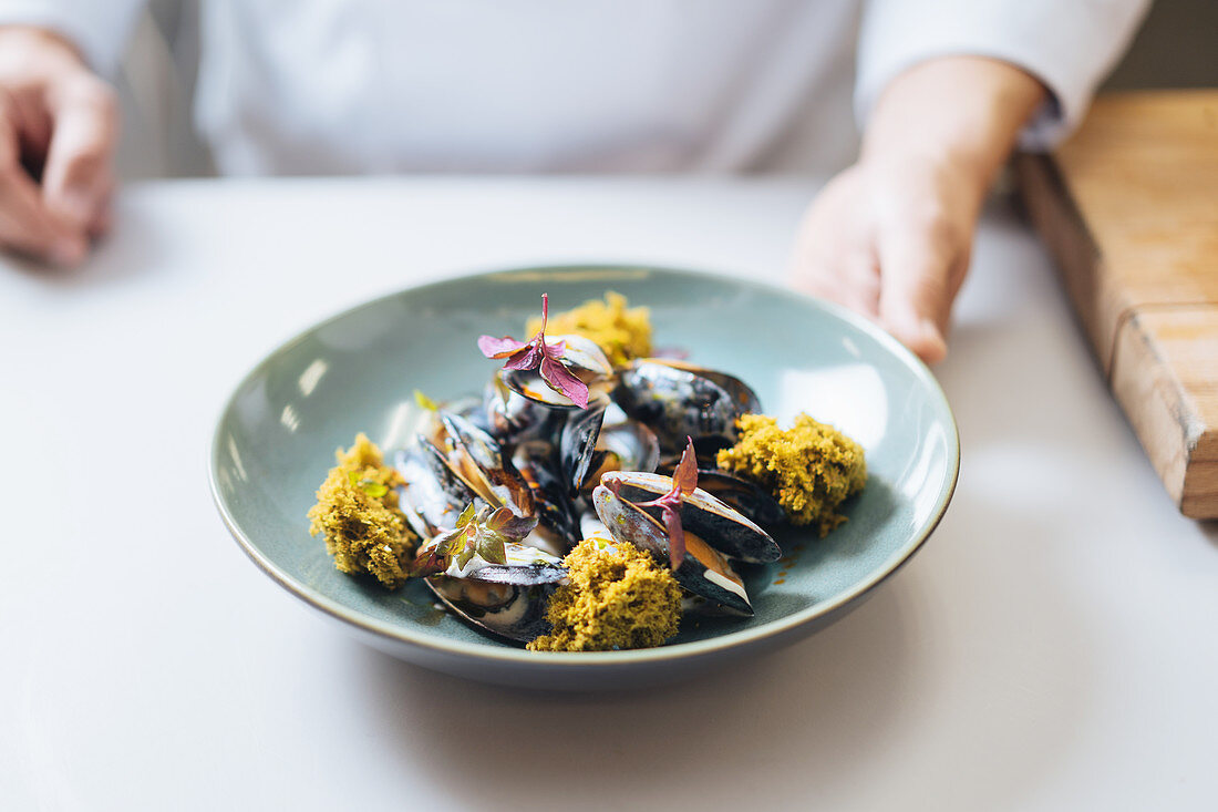 A chef serving a mussel dish