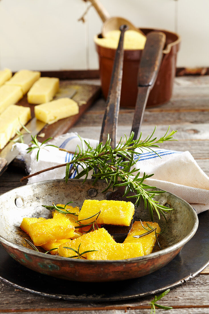 Fried polenta slices with rosemary in a vintage pan