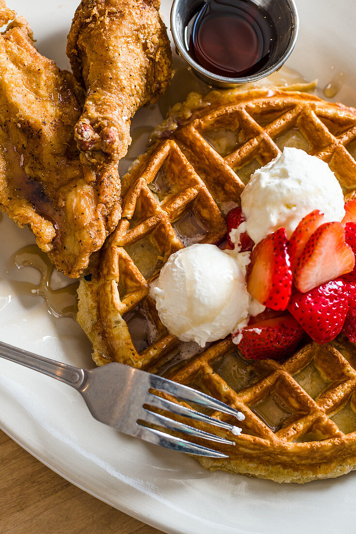 Belgian waffle topped with butter, strawberries and syrup with fried chicken