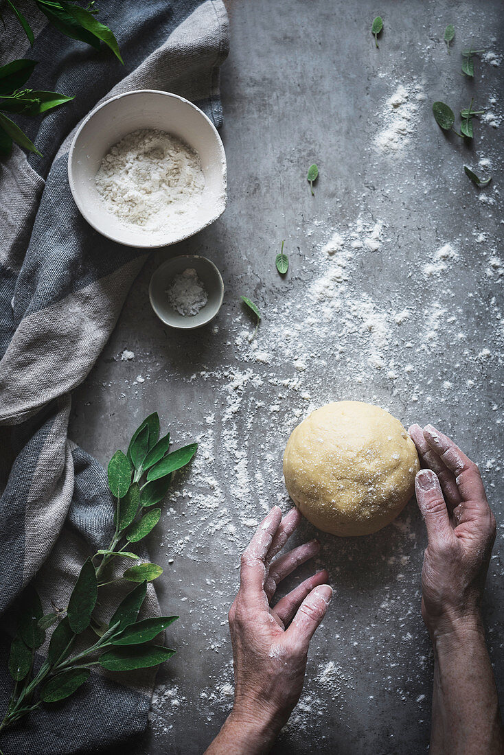 Person kneading ball of soft dough on marble counter sprinkled with flour