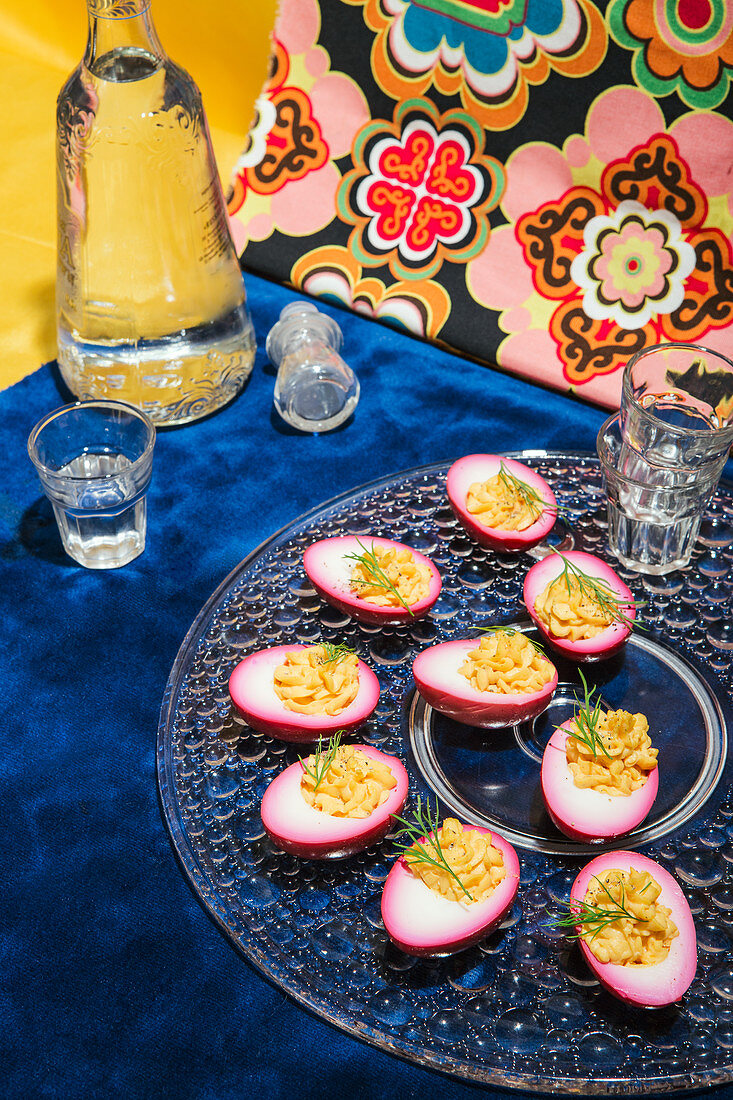 Russian eggs, garnished with dill on a glass plate, served with vodka