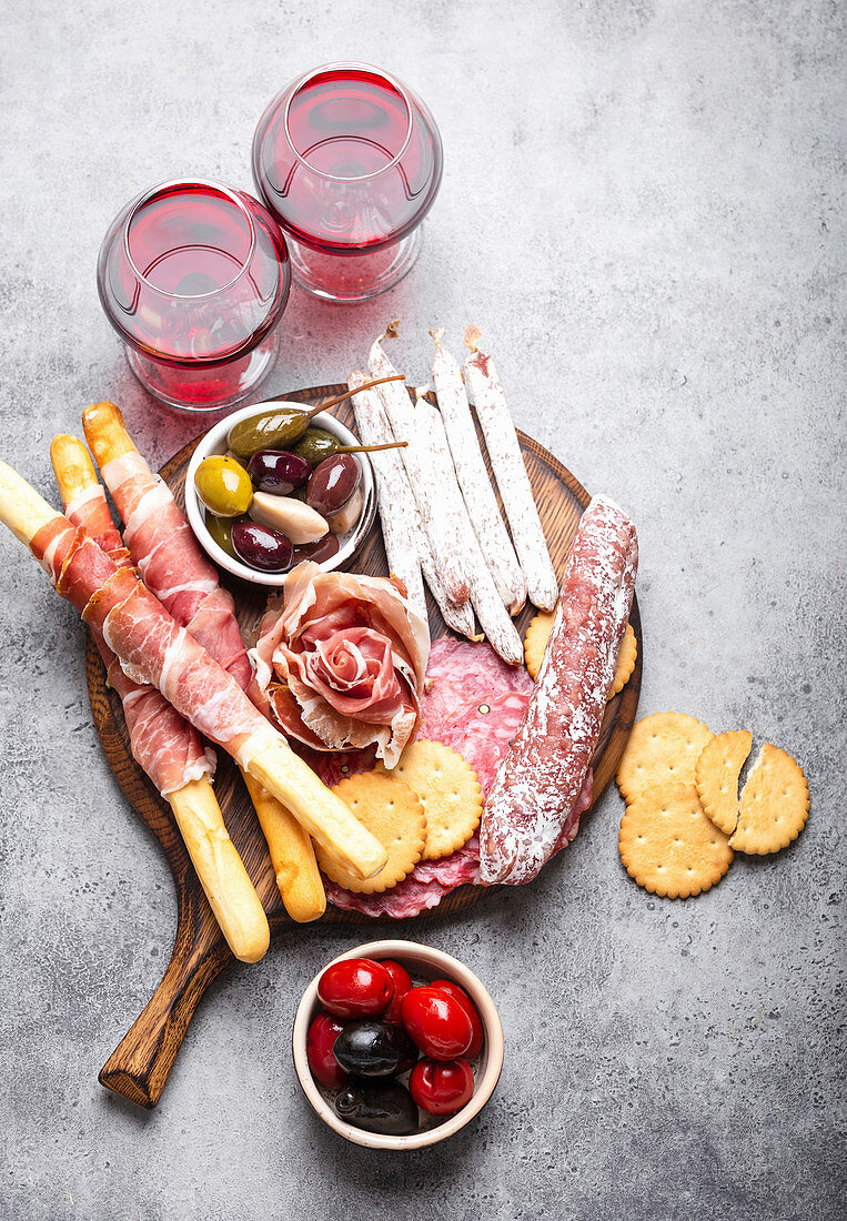 Variety of cold meat cuts and appetizers, red wine, prosciutto, jamon, salami slices, sausage, grissini and olives