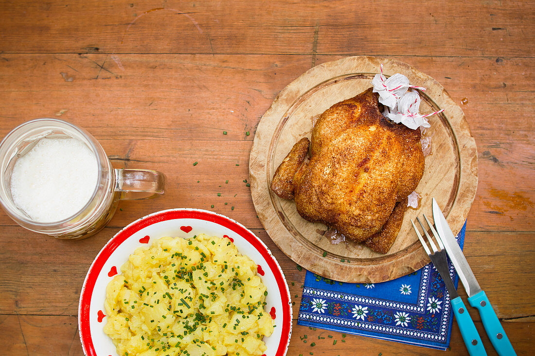 Roast chicken with potato salad and a beer mug on a beer garden table