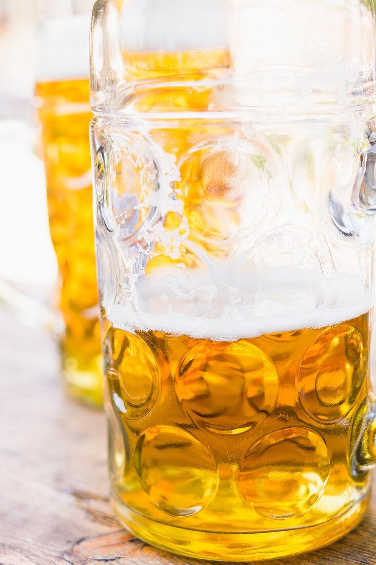 Light beer in mugs, full and half empty