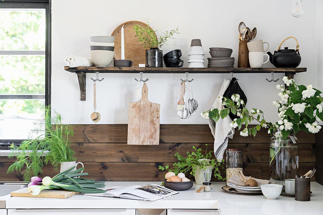 Rustic crockery on shelf in kitchen with wood-clad walls