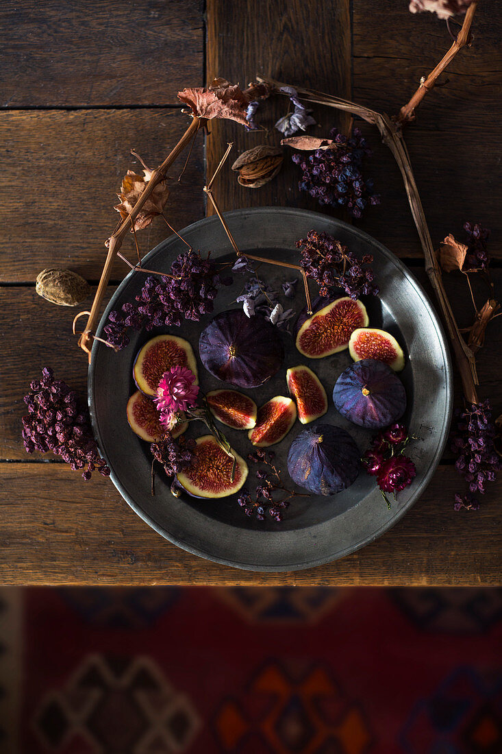 A still life with fresh figs, dried grapes and grapevine branches