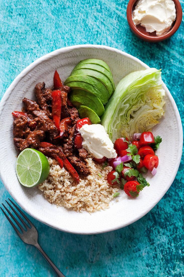 A fajita bowl with beef, cauliflower rice, avocado, tomatoes and salad