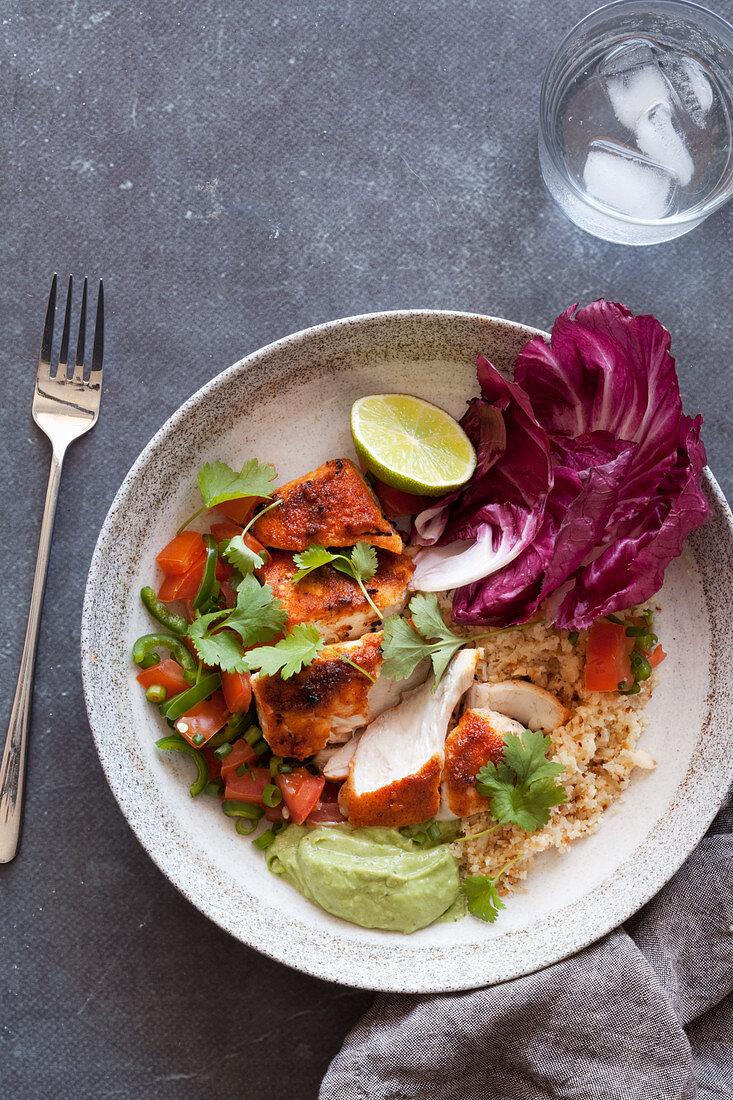 A taco bowl with fish, cauliflower rice and avocado cream