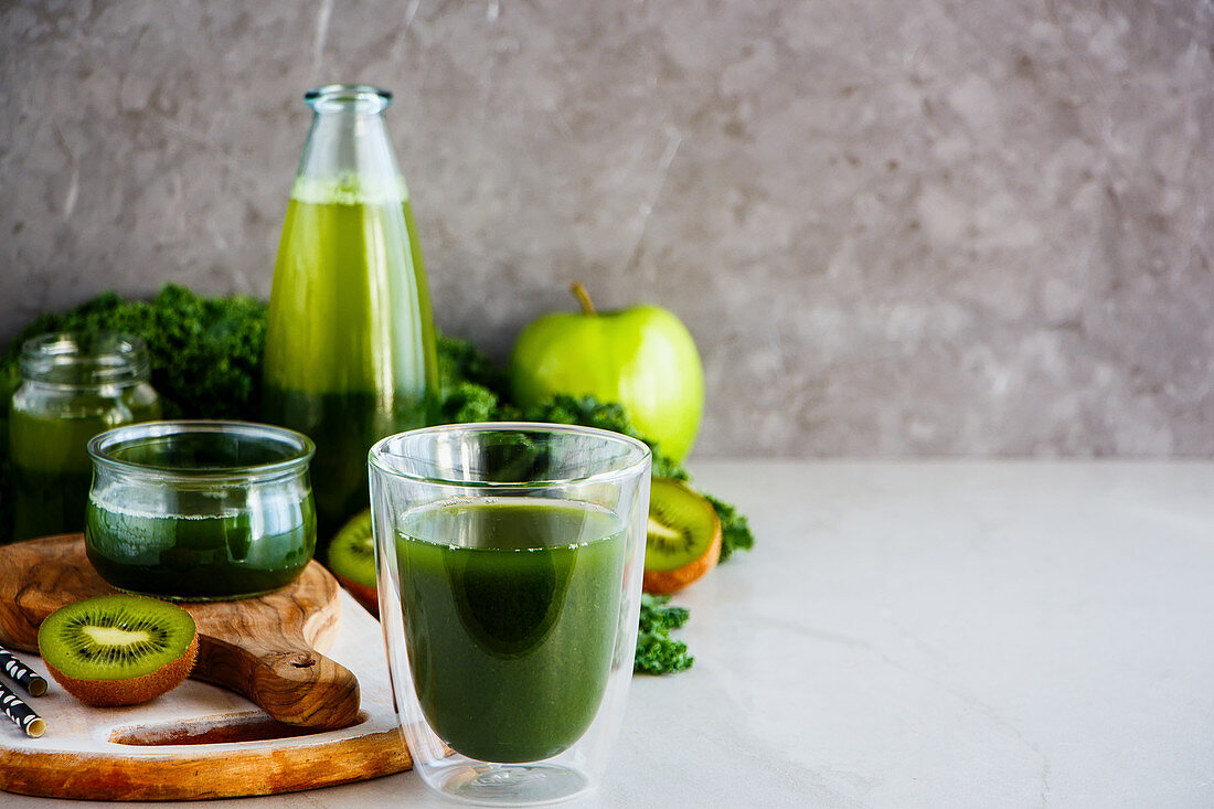 Green detox smoothies for breakfast in front of a grey background