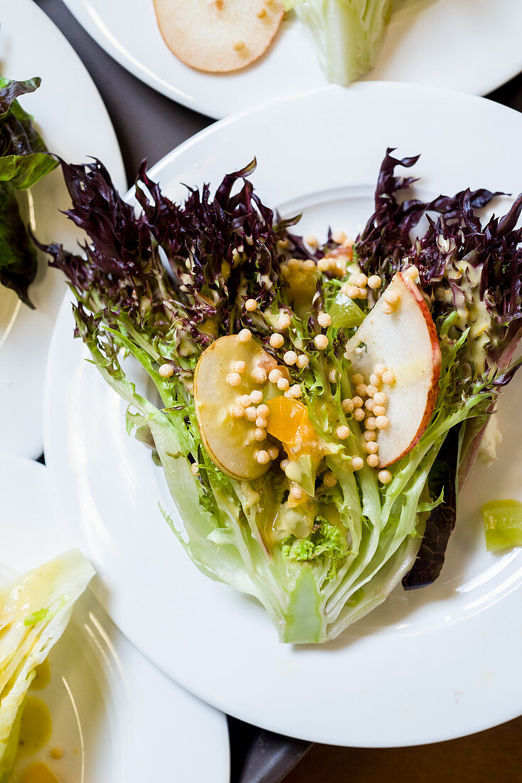 Green lettuce salad with shaved pear, apricot and barley in a vinaigrette