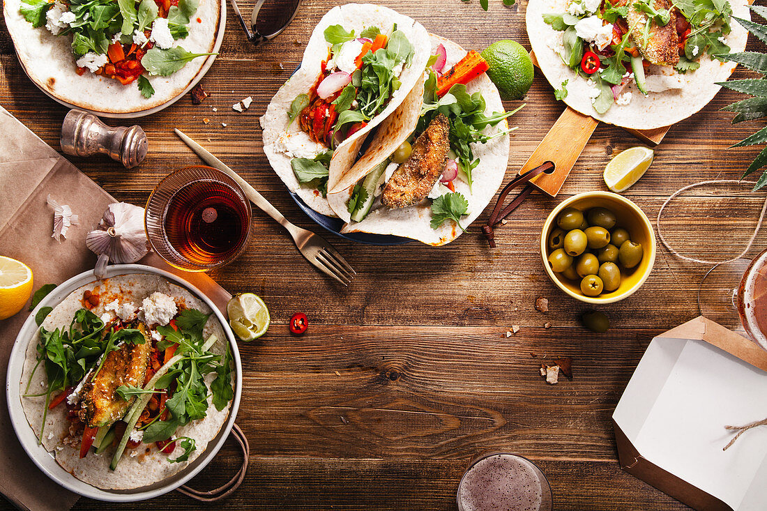 Tacos with fried avocados, tomatoes and greens