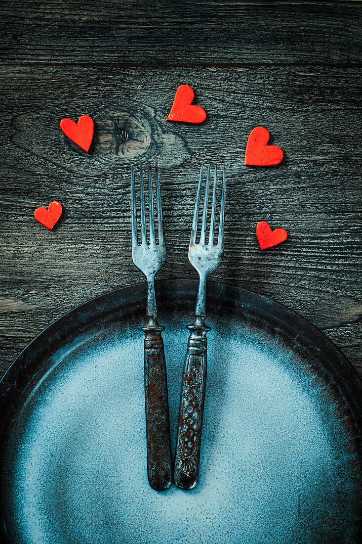 Valentine's Day dinner table setting in rustic wood style with cutlery