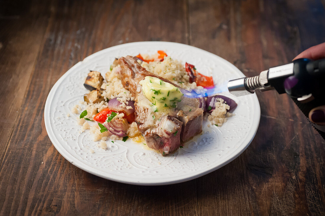 A pork chop with herb butter, couscous and vegetables